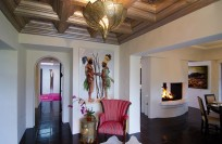 Entrance lobby with carved ceiling, open fireplace between kitchen and dining room (right), hallway to 2 lower Bedrooms (straight). Photography by Brian Hodges